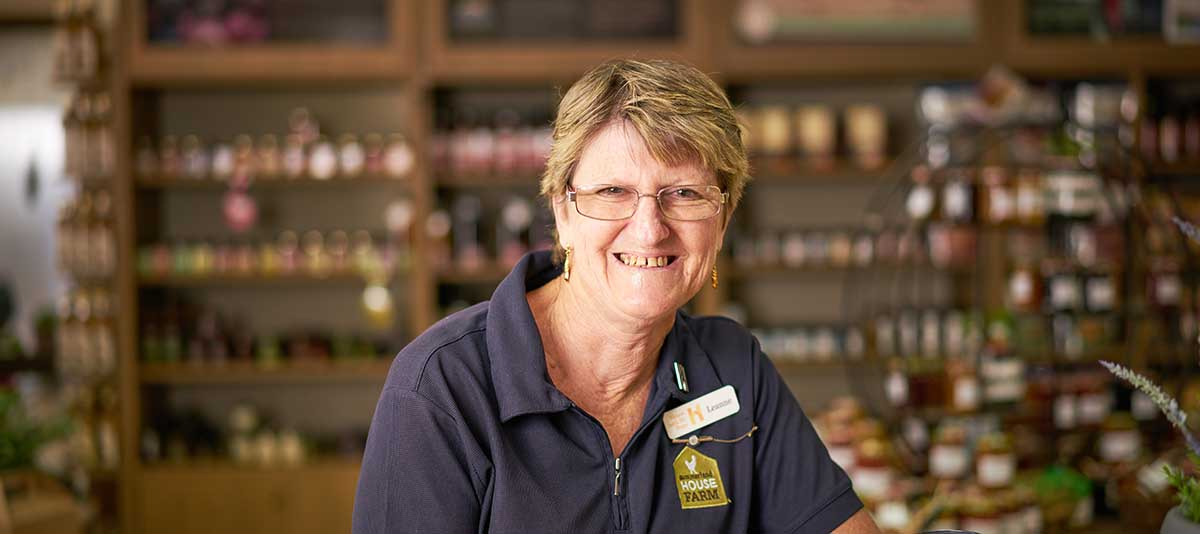 A smiling staff member stands amid produce in a grocer