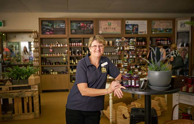 A smiling shop keeper stands near shelves of produce