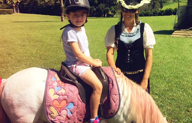 A smiling child rides a pony at a children's party