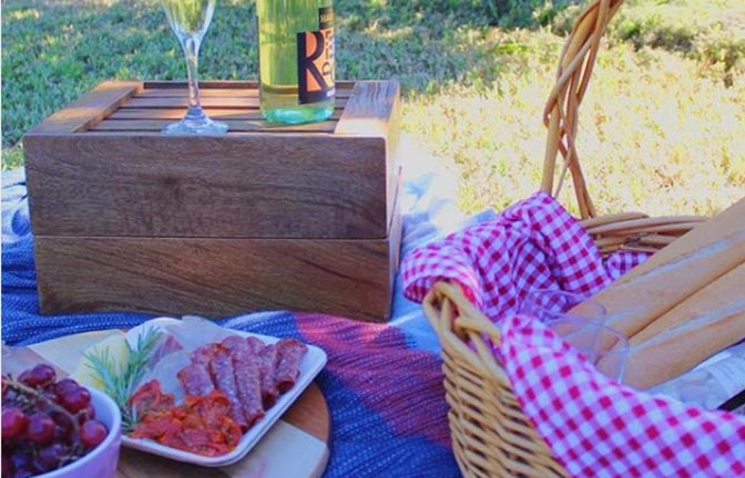 A picnic hamper and wine set on a blanket on the grass