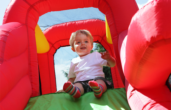 A happy young child on a jumping castle